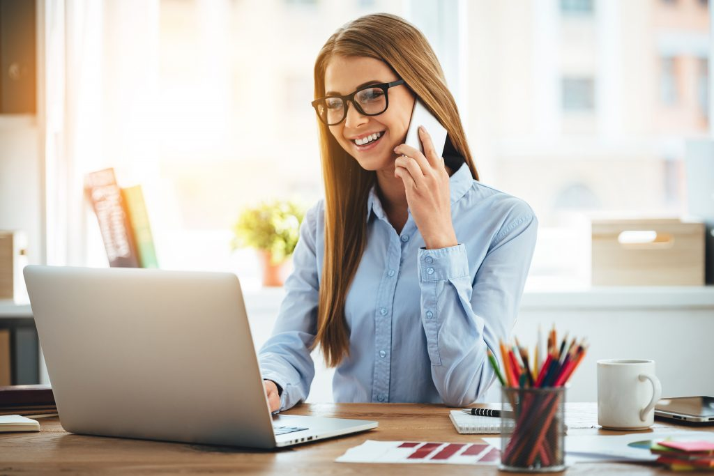 Cheerful woman in glasses talking on phone and using laptop